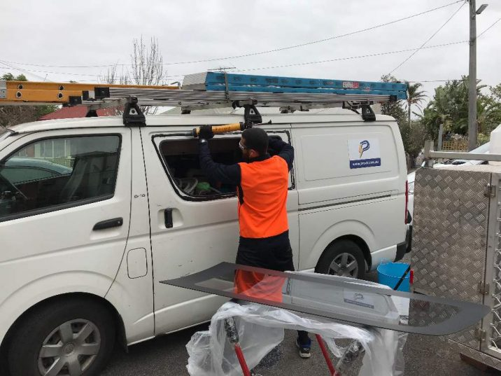 Man in orange hi vis applies black adhesive to side of a white van where a window once was.
