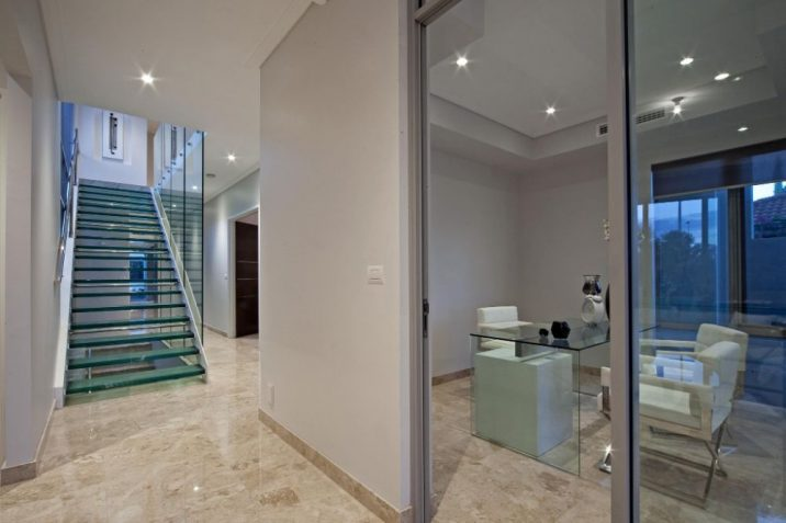 Clean white interior of a house with polished brown marble tiles and glass staircase leading to second level.