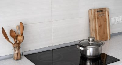 Black cooktop on a white quartz benchtop with pot, 2 wooden chopping boards and wooden spoon.