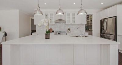 All white kitchen with stainless steel appliances, tile splashback and three pendant lights.