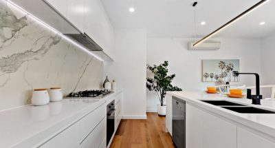 White kitchen, timber floorboards, marble splashback with black furnishes and steel appliances.