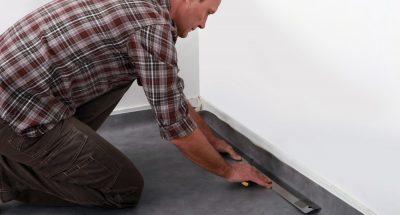 Man in checkered shirt uses long metal tool on the corners of a black linoleum floor.