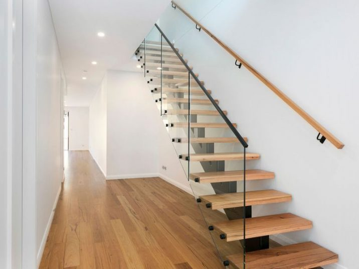 Timber floating staircase with a wooden handrail on one side and glass balustrade on the other.
