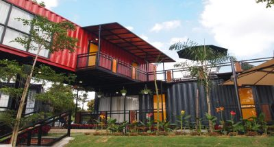 Red and black shipping container homes surrounded by a garden.