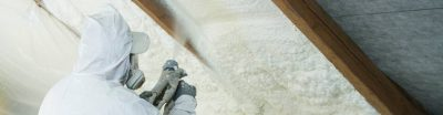 Someone spraying foam insulation into a roof