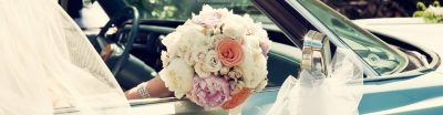 Bride with a flower bouquet in the passenger seat of a vintage wedding car
