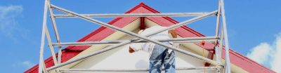 Man standing on scaffolding painting a house