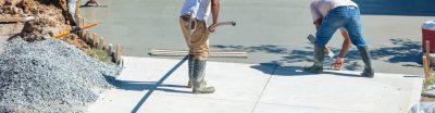 Men working on resurfacing a concrete driveway